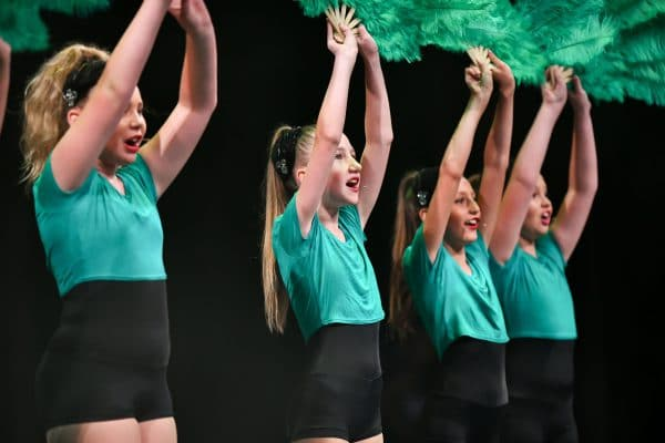 Students performing on stage with their musical theatre dance class