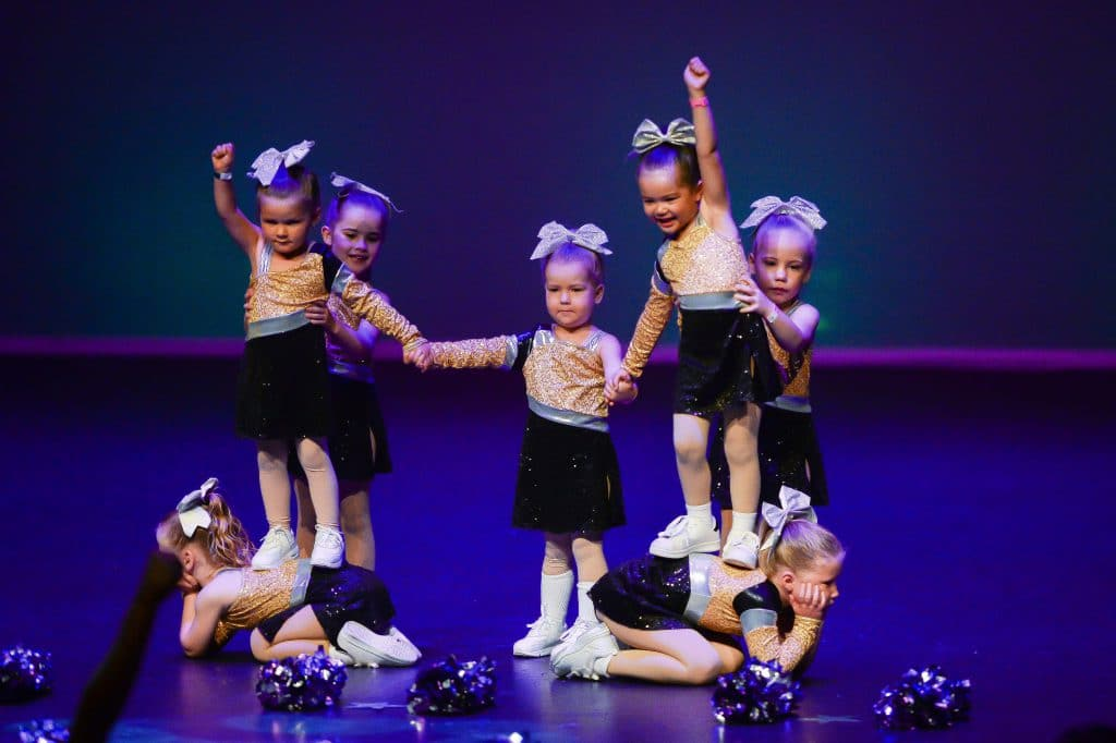 Cheerleading class performing on stage at dance concert mini dancers
